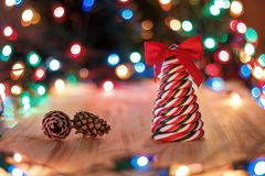 Christmas still life: candy lollipop, red bow and pine cones. Christmas still life: candy lollipop in the form of a tree with a red bow and pine cones on a Royalty Free Stock Photos