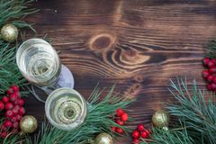 Christmas still-life, champaign, pine branches, red berries, golden balls. Christmas and New Year seasonal composition with pine tree branches, two glasses of royalty free stock image
