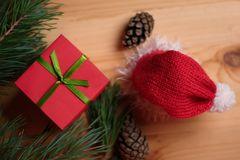 Christmas still life: Christmas hat and red gift box with pine branches and pine cones on a wooden table.  Stock Photo