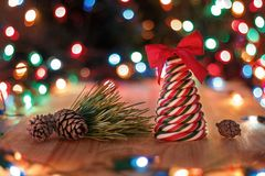 Christmas still life. Candy lollipop in the form of a tree with a red bow, a pine branch and pine cones on a wooden table on a background of Christmas garlands Stock Images