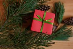 Christmas still life. Red box & x28;gift& x29;, tied with green ribbon, among the spruce twigs and cones on wooden table Royalty Free Stock Photography