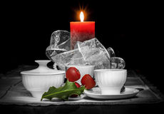 Christmas still life composition on a black background. Christmas still life composition with two white cups, a white sugar bowl, a red candle, a green holly Royalty Free Stock Photography