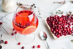 Christmas still life with cranberriy punch and blurred snow outside the window. Festive and bright royalty free stock images