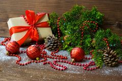 Christmas still life with gift box and fir tree branch and holiday toys. Photo of the Christmas still life with gift box and fir tree branch and holiday toys Royalty Free Stock Photo