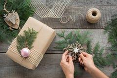 Christmas Still life of giftbox, decor, twine, fir tree, twigs. Woman prepare a gift. Stock Photo