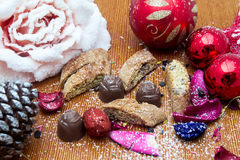 Christmas still life with ginger honey biscuits, ornaments, pine, shoes,gift ,wreaths chocolate candy on a wooden background Royalty Free Stock Photos