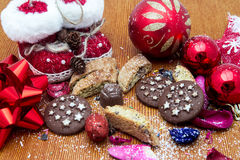 Christmas still life with ginger honey biscuits, ornaments, pine, shoes,gift ,wreaths chocolate candy on a wooden background Stock Photo