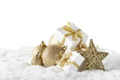 Christmas still life with golden balls, star and gift boxes lying on winter snow on a white background with copy space. New Year and Christmas. Greeting card stock photos