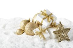 Christmas still life with golden balls, star and gift boxes lying on winter snow on a white background with copy space. New Year and Christmas. Greeting card stock images