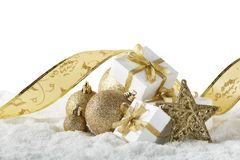 Christmas still life with golden balls, tape, star and gift boxes lying on winter snow on a white background with copy space. New Year and Christmas. Greeting royalty free stock photo