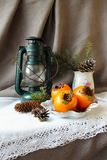 Christmas still life with a lantern and  persimmon and Royalty Free Stock Photo