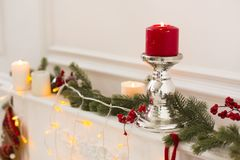 Christmas still life: metal candle holder with red burning candle, white candles, electric garland and green spruce branches Royalty Free Stock Photo