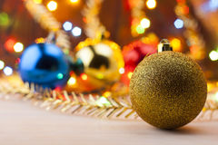 Christmas still life. New Year's toys on the table. New Year card. The golden ball in the foreground Stock Images