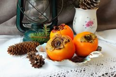 Christmas still life with persimmons Royalty Free Stock Image
