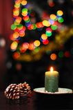 Christmas still life. With pine cones and a green candle on a background of colored lights Stock Photo
