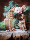 Christmas Still Life with Presents in Vintage Style. Boxes, Cord, Basket, Coniferous, Fir Tree Toys, Walnuts, Almonds on Wooden Ba Royalty Free Stock Photography