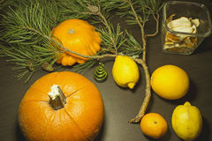 Christmas still life with pumpkins. Christmas still life: pumpkins, figurine fir tree, pine branch and citrus on a wooden table Royalty Free Stock Images