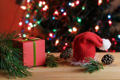 Christmas still life. Red box & x28;gift& x29; with the green bow in the pine branches, red Christmas hat and pine cones on a wooden table next to the Stock Photography