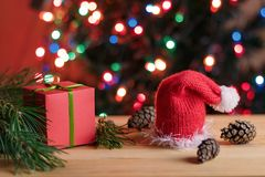 Christmas still life: red box gift, pine branches, red Christmas hat, pine cones. Christmas still life: red box gift with the green bow in the pine branches, red Royalty Free Stock Photos