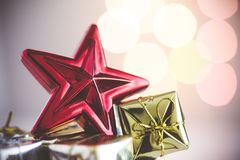 Christmas still life with red star and gifts on background lights Stock Photography