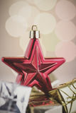 Christmas still life with red star and gifts on background lights Stock Image