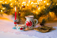 Christmas still life in the Russian style with the national dishes (Dymovskiy) branches of spruce, pine cones, red berries, lights Royalty Free Stock Photography