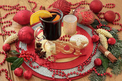 Christmas Still Life Scene. With gold glitter joy sign, mulled wine, mince pies, red bauble decorations, candles, spices, holly and snow covered fir Royalty Free Stock Photo