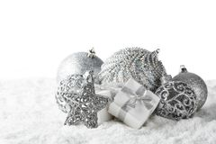 Christmas still life with silver balls, star and gift boxes lying on winter snow on a white background with copy space. Horizontal. View. New Year and Christmas stock image