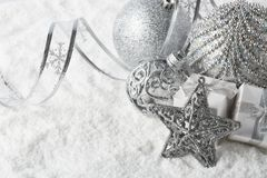 Christmas still life with silver balls, star and gift boxes lying on winter snow on a white background with copy space. Top view. New Year and Christmas royalty free stock images