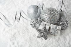 Christmas still life with silver balls, star and gift boxes lying on winter snow on a white background with copy space. Top view. New Year and Christmas stock photos