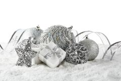 Christmas still life with silver balls, star and gift boxes lying on winter snow on a white background. Horizontal view. New Year. And Christmas royalty free stock images