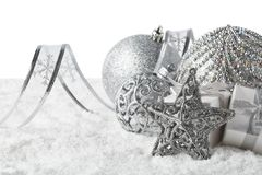 Christmas still life with silver balls, star and gift boxes lying on winter snow on a white background. Horizontal view. New Year. And Christmas stock images
