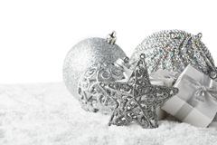 Christmas still life with silver balls, star and gift boxes lying on winter snow on a white background. Horizontal view. New Year. And Christmas royalty free stock image