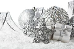 Christmas still life with silver balls, star and gift boxes lying on winter snow on a white background. Horizontal view. New Year. And Christmas stock photography