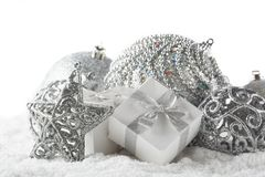 Christmas still life with silver balls, star and gift boxes lying on winter snow on a white background. Horizontal view. New Year. And Christmas stock image