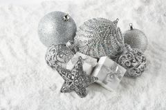 Christmas still life with silver balls, star and gift boxes lying on winter snow on a white background. Top view. New Year and. Christmas royalty free stock photo