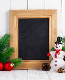Christmas still life with snowman and firtree on wooden board Stock Photos
