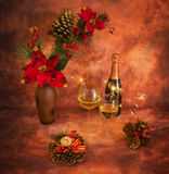 Christmas still life with sparklers, ornaments, champagne and ca. Ndle in warm colors stock photo