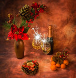 Christmas still life with sparklers, ornaments, champagne, tangerines. In warm colors stock image