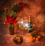 Christmas still life with sparklers, ornaments, champagne, tangerines. In warm colors royalty free stock photography