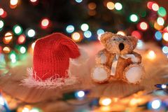 Christmas still life. A Teddy bear Christmas red hat on a wooden table on a background garlands Stock Photos