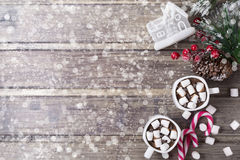 Christmas still life - two cups of hot chocolate with marshmallow, candies, toy house and branch of fir with berries Royalty Free Stock Photos