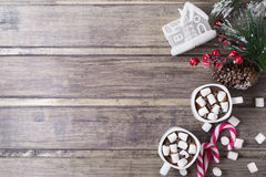 Christmas still life - two cups of hot chocolate with marshmallow, candies, toy house and branch of fir with berries Royalty Free Stock Image