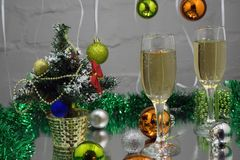 Christmas still life - Two glasses of champagne with red Xmas decorations on Christmas tree and blurred yellow background Royalty Free Stock Photos