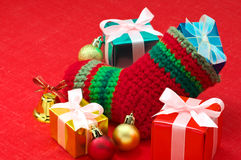 Christmas stocking and colorful presents on red fa Stock Photo