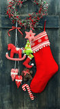 Christmas stocking and handmade toys hanging. Over rustic wooden background. vintage style toned picture Royalty Free Stock Photo