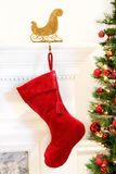 Christmas stocking hanging mantelpiece. Red velvet stocking hanging on the mantelpiece Royalty Free Stock Photography