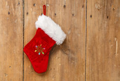 Christmas stocking hanging on an old pine wooden door. Christmas stocking hanging on a light colored old pine wooden door. Copyspace to the right Stock Photos