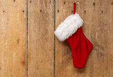 Christmas stocking hanging on an old pine wooden door. Christmas stocking hanging on a light coloured old pine wooden door Royalty Free Stock Images