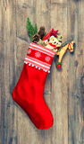 Christmas stocking with nostalgic vintage toys decoration. And pine branch over wooden background. vintage style toned picture royalty free stock photos
